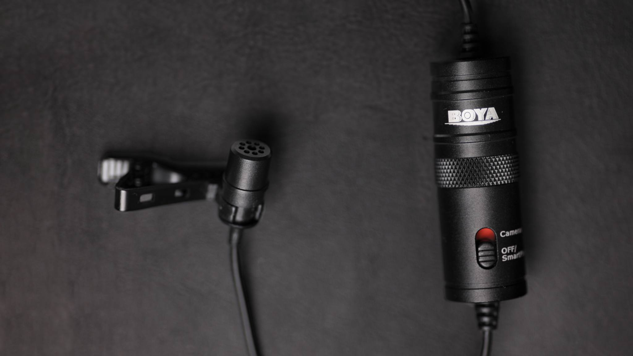 All Geared Up boya-by-m1-dark-banner Get Better Audio With The Multi Functional BOYA BY-M1 Lavalier Microphone audio hardware video  sound microphone review microphone lavalier mic lav mic gear review audio